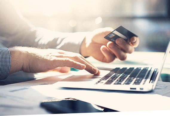 Ein Mann tippt am Laptop die Daten seiner Kreditkarte ein und bindet damit sein Bezahlverfahren über das SAP Digital Payments Add-on ein.
